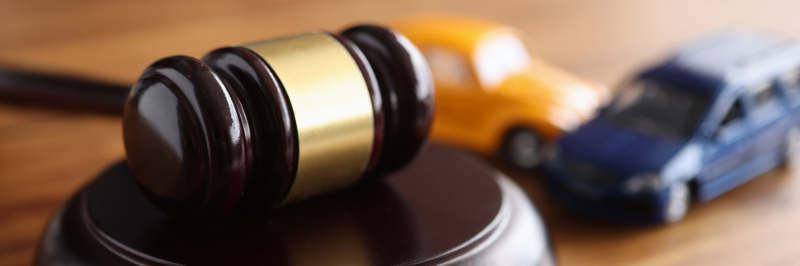 Judges wooden gavel lying on table near toy machines closeup